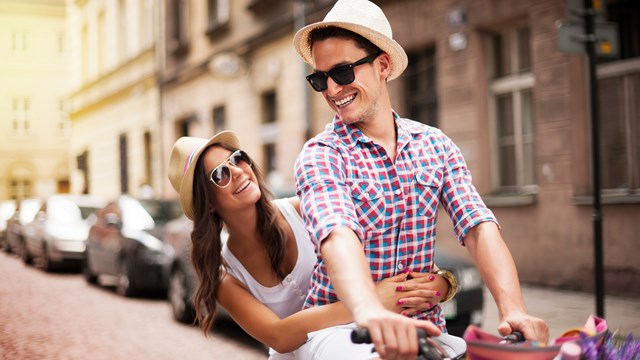 People in Action: Caucasian couple cycling down the street wearing hats and sunnies.